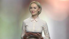 Frauensprecher von mittlerem Alter, der digitale Tablette hält stock footage