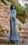 Frauenstatue im Eze Dorf nahe Kirchegebäude Stockbilder