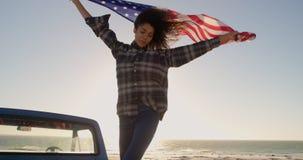 Frauenstellung mit wellenartig bewegender amerikanischer Flagge auf einem LKW 4k der Auswahl oben stock video