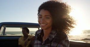 Frauenstellung nahe Kleintransporter auf dem Strand 4k stock footage