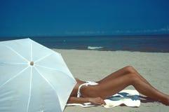 Frauenstrand und weißer Regenschirm Stockfotos