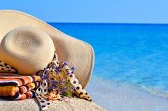 Frauenstrandhut, helles Tuch und Blumen gegen blauen Ozean Stockfotografie