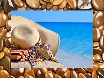 Frauenstrandhut, helles Tuch und Blumen gegen blauen Ozean Lizenzfreies Stockfoto