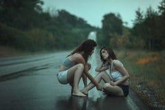 Frauenstreit im Regen auf der Straße Stockfotos