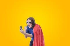 Frauensuperheld, der am Telefon mit rotem Kap schreit Stockfotografie
