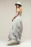 Frauentanzen im grauen Kleid und im Hut Stockfotografie
