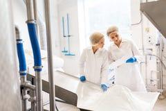 Frauentechnologen, die an der Eiscremefabrik arbeiten stockfotos
