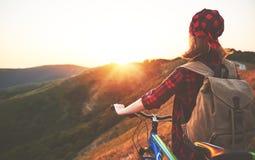Frauentourist auf einem Fahrrad an der Spitze des Berges bei Sonnenuntergang draußen Lizenzfreies Stockfoto