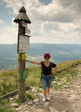 Frauentourist, der den Beitrag mit Informationen steht und übersieht stockfoto