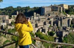 Frauentourist, der Foto von mittelalterlicher Tuff Sorano-Stadt in Italien macht stockbilder