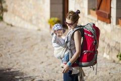 Frauentourist, der ihren kleinen Sohn im Riemen trägt stockbilder