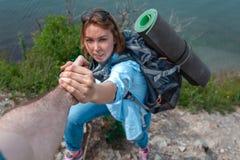 Frauentourist ergreift die Hand seines Freunds Im Hintergrund, im Abgrund und im Meer Das Konzept der Freundschaft und das gegens lizenzfreies stockfoto