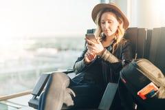Frauentourist im Hut, mit Rucksack sitzt am Flughafen nahe Fenster, benutzt Smartphone Warteflache Landung des Hippie-Mädchens Lizenzfreie Stockfotografie
