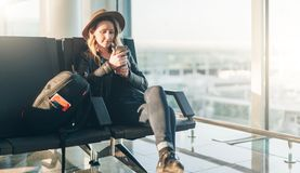 Frauentourist im Hut, mit Rucksack sitzt am Flughafen nahe Fenster, benutzt Smartphone Warteflache Landung des Hippie-Mädchens Stockfotos