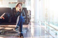 Frauentourist im Hut, mit Rucksack sitzt am Flughafen nahe Fenster, benutzt Smartphone Warteflache Landung des Hippie-Mädchens Lizenzfreie Stockbilder
