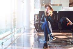 Frauentourist im Hut, mit Rucksack sitzt am Flughafen nahe Fenster, benutzt Smartphone Warteflache Landung des Hippie-Mädchens Lizenzfreies Stockbild
