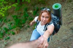 Frauentourist klettert die Steigung und ergreift die Hand seines Freunds Freundschaft und gegenseitiges Stützkonzept Tourismus un stockfotos