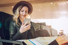 Frauentourist mit Rucksack sitzt am Flughafen, benutzt den Smartphone und hält Bestimmungsortkarte Mädchen wartet auf flache Land Stockfoto