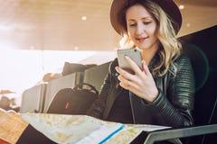 Frauentourist mit Rucksack sitzt am Flughafen, benutzt den Smartphone und hält Bestimmungsortkarte Mädchen wartet auf flache Land Lizenzfreies Stockfoto