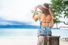 Frauentourist am tropischen Strand, der Ozean ihre Ferien betrachtet Stockfotografie