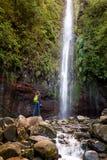 Frauentourist und Hauptwasserfall am levada 25 Brunnen in Rabacal, Madeira-Insel Lizenzfreies Stockfoto