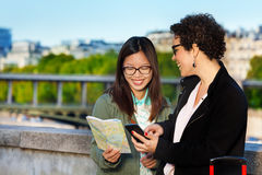 Frauentouristen, die eine Papierkarte und ein intelligentes Telefon halten lizenzfreie stockfotografie