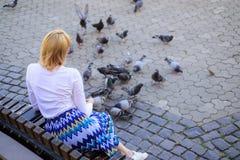 Frauentouristen- oder -bürgerwurf zerkrümelt für Tauben Entspannende Stadtplatz- und Fütterungstauben der Mädchenblondine Mädchen lizenzfreie stockfotos