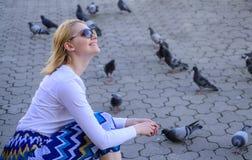 Frauentouristen- oder -bürgerwurf zerkrümelt für Tauben Fütterungstaubenvögel des Mädchens Gruppentauben auf Stadtplatzwartefestl lizenzfreie stockbilder