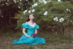 Frauenträume des Sitzens unter einem Busch stockbilder