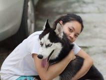 Frauenumarmungssibirischer husky Lizenzfreie Stockbilder