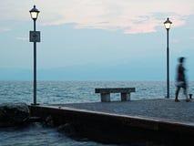 Frauenunschärfe an der Bank durch See an der blauen Stunde lizenzfreie stockbilder