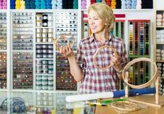 Frauenverkäufer, der Stickereiring in nähender Abteilung hält Lizenzfreie Stockfotos