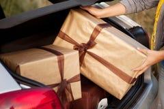 Frauenverlassen ein ihr Auto mit Geschenken Stockbild