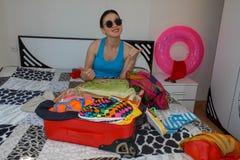 Frauenverpackung, die für Sommerferien sich vorbereitet Schönes Mädchen mit einem Rotkoffer liebt zu reisen Stockbilder