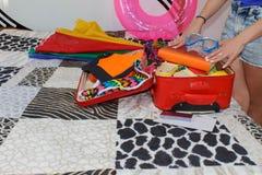 Frauenverpackung, die für Sommerferien sich vorbereitet Schönes Mädchen mit einem Rotkoffer liebt zu reisen Lizenzfreie Stockbilder