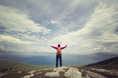 Frauenwanderer, der auf Bergspitze wandert Lizenzfreie Stockbilder