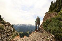 Frauenwanderer, der auf Bergspitzeklippe wandert Lizenzfreie Stockfotos