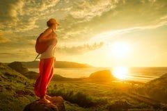 Frauenwanderer, der auf die Oberseite steht und Sonnenuntergang über Meer genießt Stockbilder