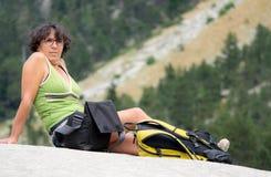 Frauenwanderer, der auf einem Felsen sitzt Stockfoto