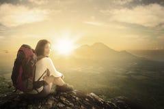 Frauenwanderer, der auf einer Bergspitze sitzt Lizenzfreies Stockfoto