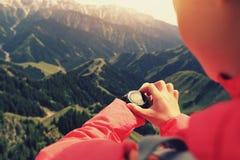 Frauenwanderer, der den Höhenmesser auf Sportuhr an der Bergspitze überprüft lizenzfreies stockbild