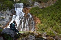 Frauenwanderer, der Foto des Wasserfalls macht stockfoto