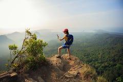 Frauenwanderer, der Foto mit dem Mobiltelefon wandert auf Bergspitze macht Lizenzfreies Stockbild