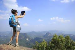 Frauenwanderer, der Foto mit Digitalkamera an der Bergspitze macht Stockfotografie