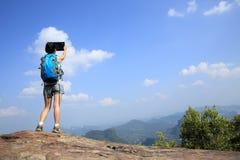 Frauenwanderer, der Foto mit Digitalkamera an der Bergspitze macht Stockfotos