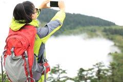 Frauenwanderer, der Foto mit Handy macht Stockbilder