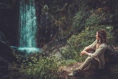 Frauenwanderer, der nahe Wasserfall im tiefen Wald sitzt Lizenzfreie Stockfotografie