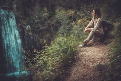 Frauenwanderer, der nahe Wasserfall im tiefen Wald sitzt Lizenzfreies Stockfoto