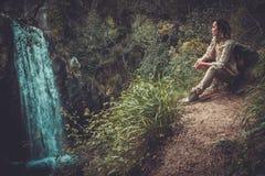 Frauenwanderer, der nahe Wasserfall im tiefen Wald sitzt Stockbilder
