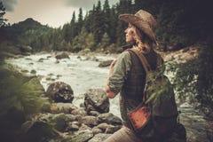 Frauenwanderer, der nahe wildem Gebirgsfluss geht Stockfotografie